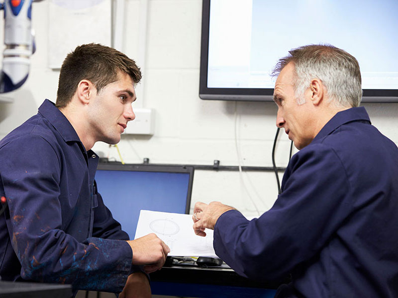 Engineer Showing Trainee Plans In Class To Promote Plc Courses